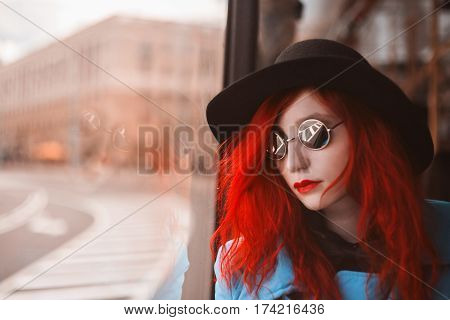 Woman with red curly hair in a blue coat and black round glasses riding on the bus. Red-haired girl with pale skin and bright appearance with black hat on head and looking out the window. Street style