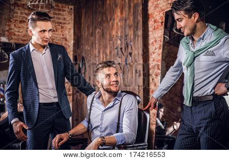 Three young elegant positive friends pose in interior of barbershop.