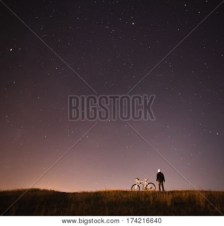 starry sky night photography astrophotography the silhouette of a man a man standing next to a mountain bike on the background of a starry sky the white bicycle