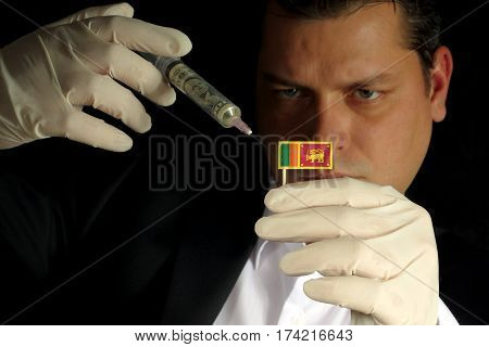 Young Businessman Gives A Financial Injection To Sri Lankan Flag Isolated On Black Background
