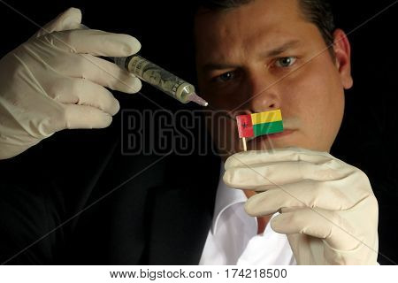Young Businessman Gives A Financial Injection To Guinea Bissau Flag Isolated On Black Background