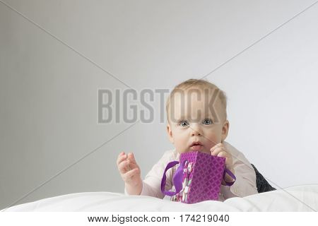 Adorable little baby lying on the white blanket and holding purple gift bag in his hands. Horisontal studio shot. Copy space