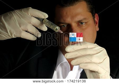 Young Businessman Gives A Financial Injection To Panamanian Flag Isolated On Black Background