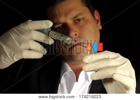 Young Businessman Gives A Financial Injection To Mongolian Flag Isolated On Black Background