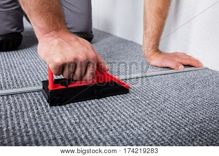 Close-up Of Craftsman's Hands Laying Carpet On The Floor