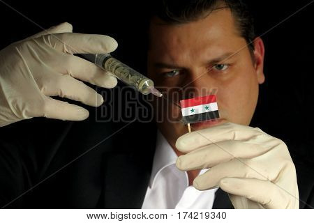 Young Businessman Gives A Financial Injection To Syrian Flag Isolated On Black Background
