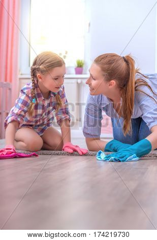 mother and daughter cleaning up the floor