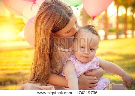 cute little sister caring baby with balloons on party