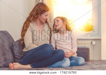mother daughter talking on couch at home