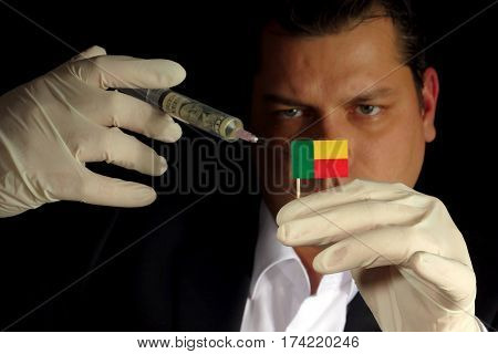 Young Businessman Gives A Financial Injection To Benin Flag Isolated On Black Background