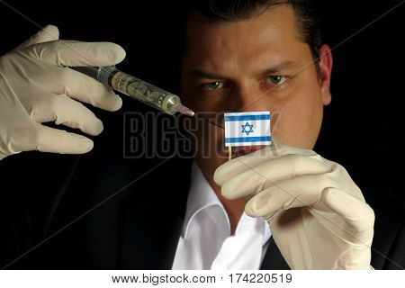 Young Businessman Gives A Financial Injection To Israeli Flag Isolated On Black Background