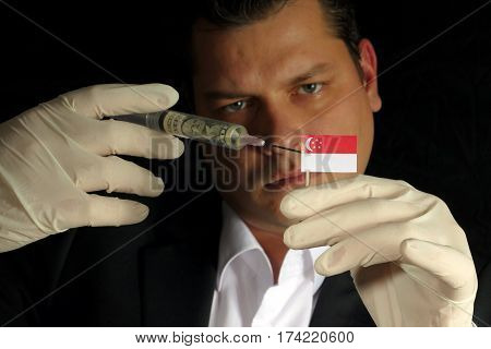 Young Businessman Gives A Financial Injection To Singaporean Flag Isolated On Black Background
