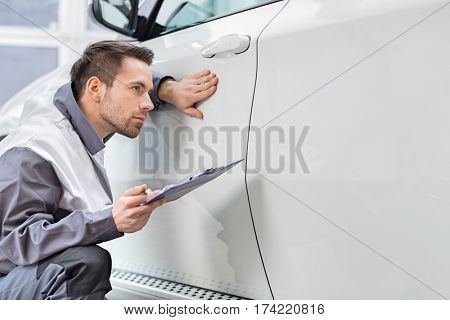 Young male repair worker examining car in automobile repair shop