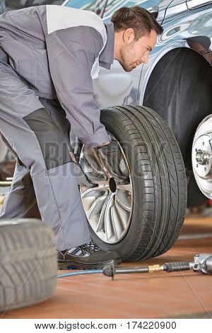 Full length of male mechanic fixing car's tire in repair shop
