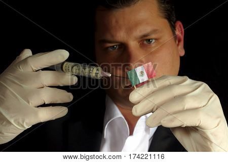 Young Businessman Gives A Financial Injection To Mexican Flag Isolated On Black Background