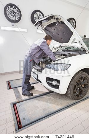 Full length side view of male automobile mechanic repairing car engine in repair shop