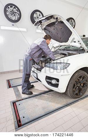 Full length side view of male automobile mechanic repairing car engine in repair shop