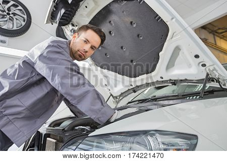 Portrait of confident male repair worker repairing car engine in repair shop