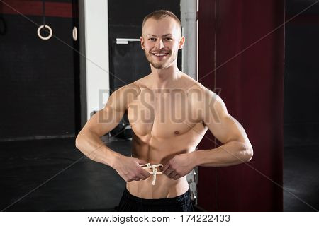 Portrait Of A Athlete Man Measuring His Body Fat With Caliper In The Gym