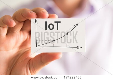 Businessman Holding A Card With Iot Internet Of Things Rising Arrow And Chart