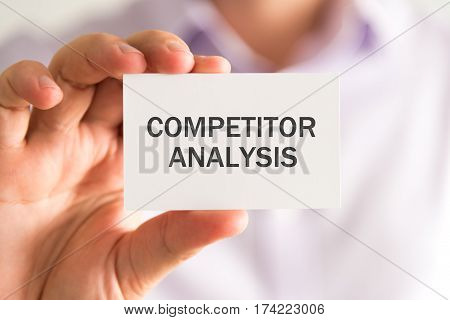 Businessman Holding A Card With Competitor Analysis Message