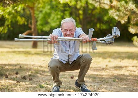 Old man with vitality and crutches in rehab having fun