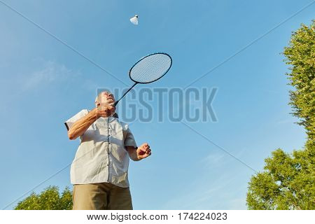 Old man with shuttlecock and racket doing sport in summer