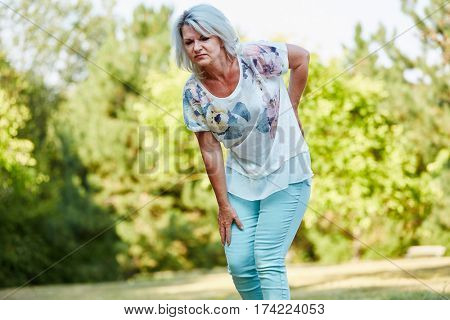 Old woman with lumbago pain while walking in the nature