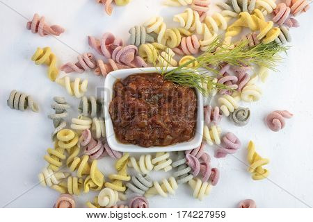 Curly and twisted pasta shapes on a cutting board in various colors of pink yellow green and white and marinara sauce