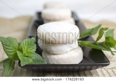 Lemon and Vanilla shortbread cookies stacked on a black ceramic dish on a lace doily and garnished with mint