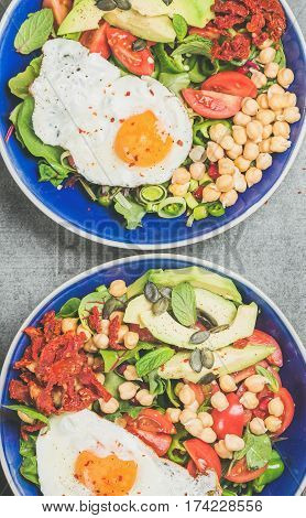 Close-up of healthy breakfast with fried egg, chickpea sprouts, seeds, vegetables and greens in bowls over grey concrete background, top view. Clean eating, healthy lifestyle, vegetarian food concept