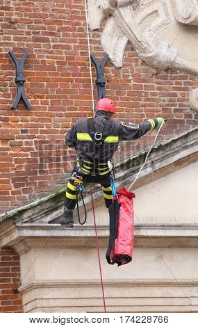 brave firefighters climbing with ropes and climbing equipment on a building