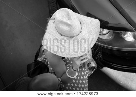 VILLA SAN GIOVANNI, ITALY - AUGUST 10, 2016: high view of a lady with straw hat is drinking from a plastic bottle of Coca-Cola supported by hand with pink nail polish (black-white)
