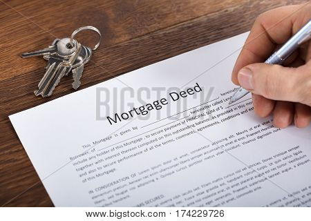 High Angle View Of A Person Hand Filling Mortgage Document On Wooden Desk