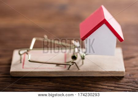 Close-up Of A House Model On Mousetrap At Wooden Desk