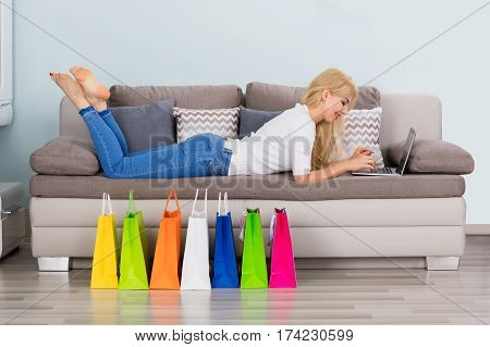 Young Happy Woman Lying On Sofa Using Laptop With Colorful Shopping Bags On Floor. Online Shopping Concept