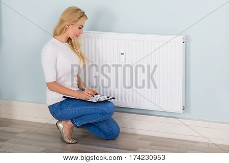 Young Woman Maintaining Records Of Digital Thermostat On Clipboard At Home