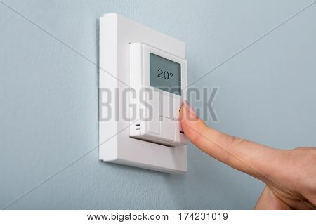 Close-up Of Person Hand Setting The Thermostat At House