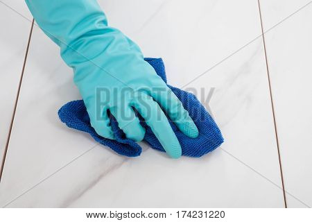 Close-up Of A Person Wearing Glove Cleaning Tiled Floor With Cloth