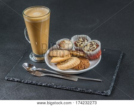 right side view on an aromatic coffee latte with three buttered muffins and petit fours on a white saucer with a spoon and forks the whole on a black stone plate sweet set