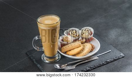 left side view on an aromatic coffee latte with three buttered muffins and petit fours on a white saucer with a spoon and forks the whole on a black stone plate sweet set