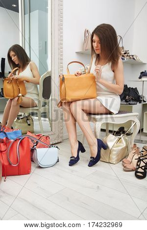 young Woman trying on shoes and bags