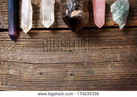 Multiple semi precious gemstones on wooden board