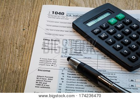 Tax preparation form US 1040 with calculator and pen on wooden table
