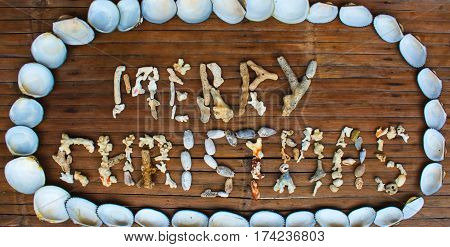 Merry Christmas inscription handmade with sea corals on wooden background. Merry Christmas greeting by corals. Seaside Christmas beach decoration. Grunge Christmas banner with sea shells and corals