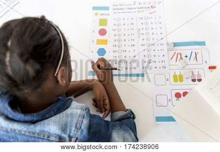 Kid Concentrating with Mathematics Homework Learning