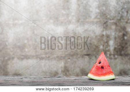 Fresh watermelon slice on wooden table with old brick wall background