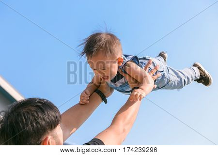 Happy family - father having fun throws up in the air child. father's day concept.
