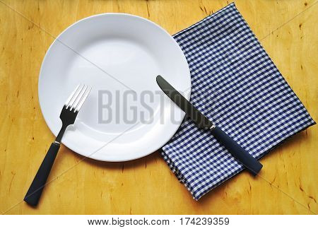 Plate and cutlery on a wooden background