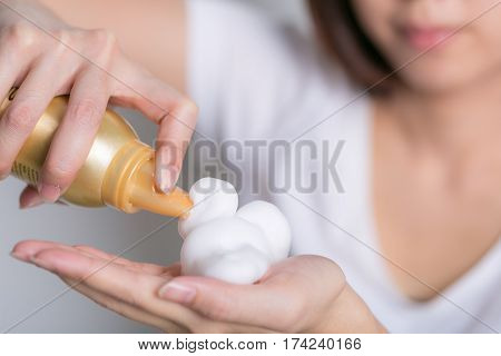 Close-up of hairdresser hairstylist female hand with hair mousse spray.